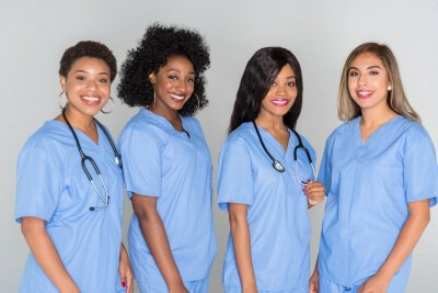 four nurses smiling