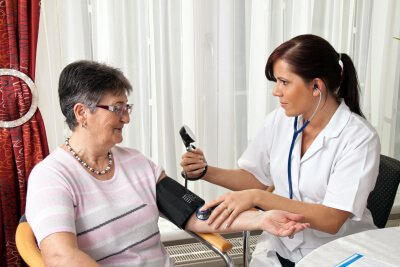 nurse checking the blood pressure of the senior woman